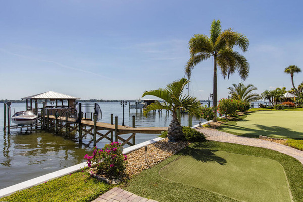 covered dock and boat lift on river behind luxury home yard