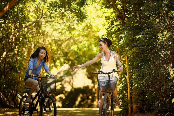 two young women, one with her right arm raised, on bikes