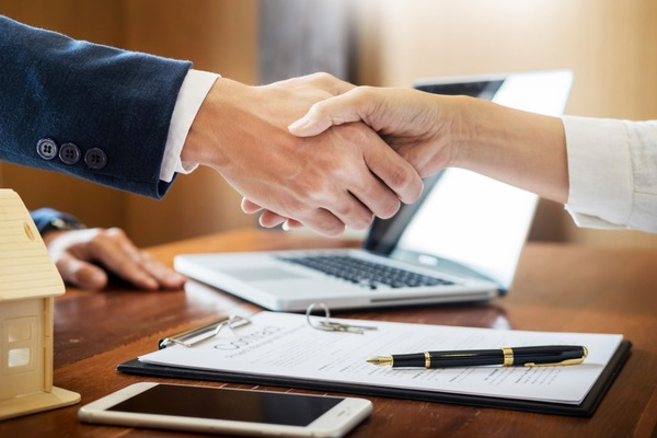 close up of man and woman shaking hands over property deal