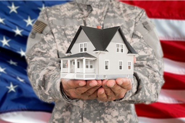 person in military uniform holding a model home