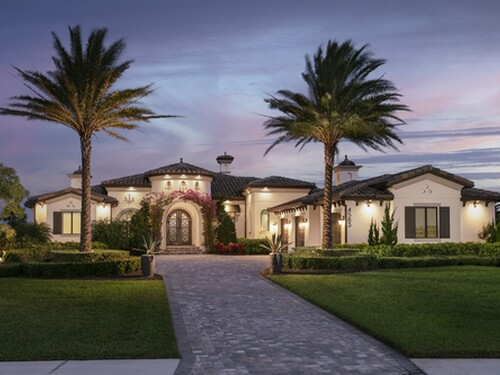 Twilight front elevation imaging motor court, side entry garage and bougainvillea accented entryway.